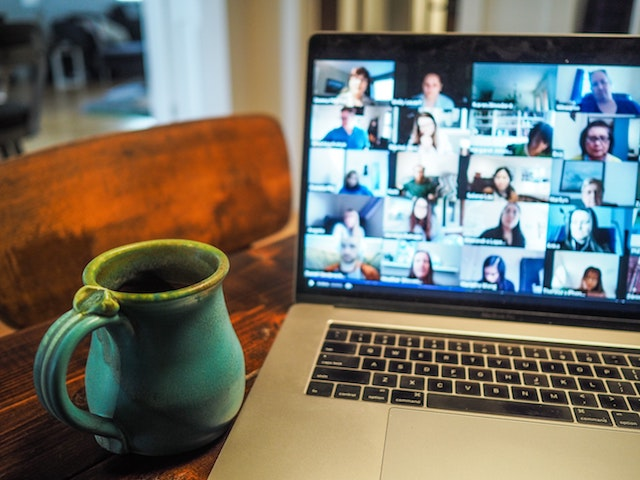Open laptop w/ online conference, zoom, meeting on screen.  Pottery cup on the right.  Table is wood.